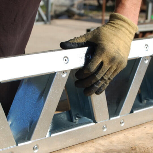 Light Gauge Steel Being Being Handled By A Man Wearing Gloves