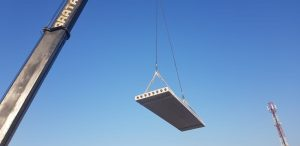 Hollow Core Concrete slap being lowered into place by a crane