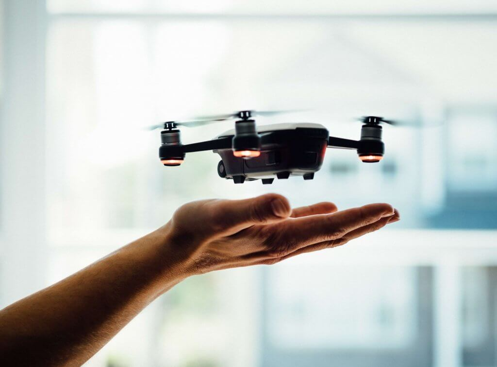 Person flying a drone above their hand