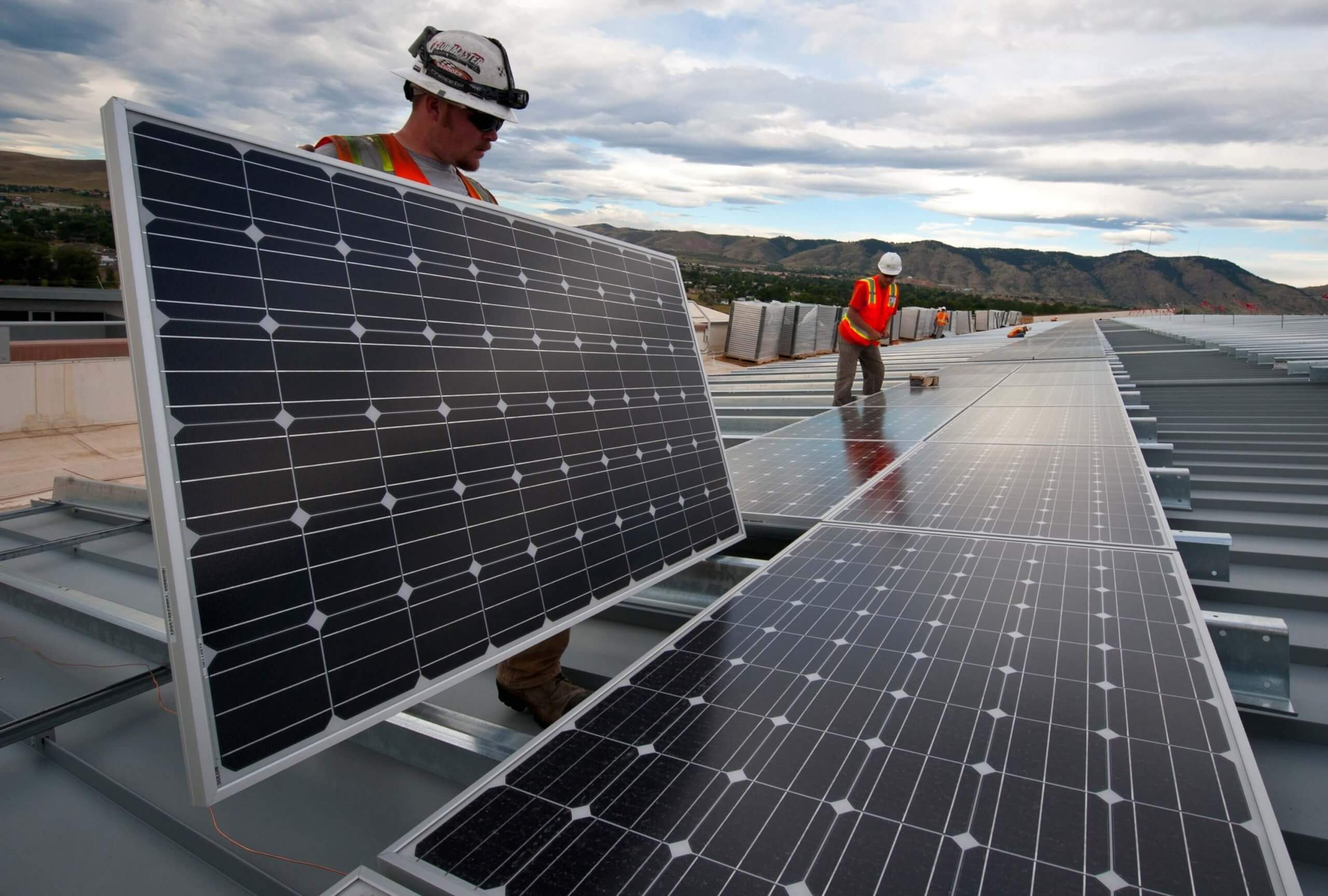 Construction workers putting solar panels on a roof